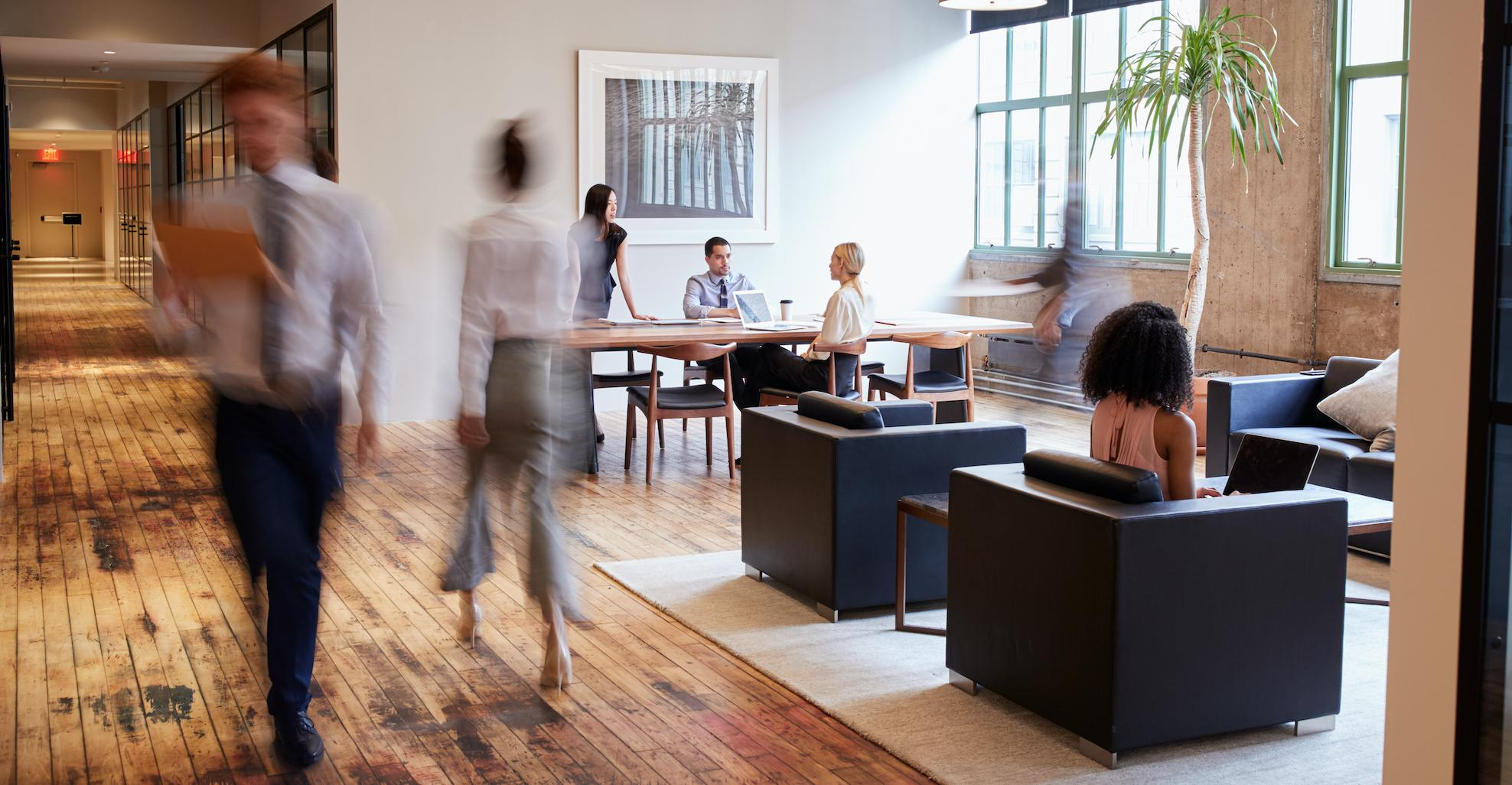 office space with wood floors and people walking
