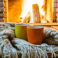 cozy hot drinks and blanket by fire at home