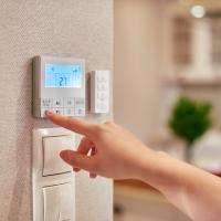 womans hand adjusting thermostat