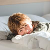 young boy in bed waking up happy